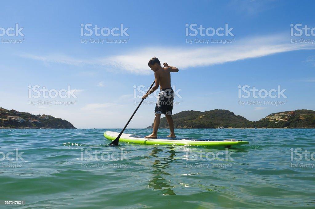 Child paddling stand up board. stock photo