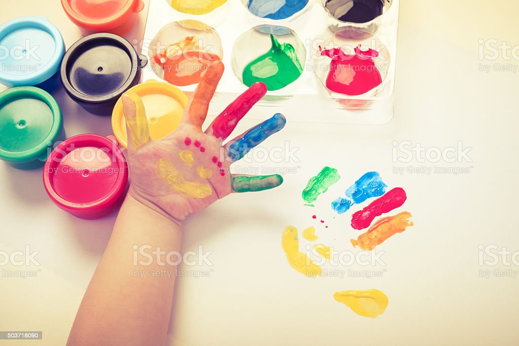 Child paint her palm with smiling face various colors. stock photo