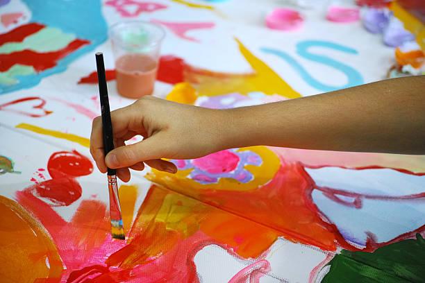 child paintbrushing on canvas - clase de arte fotografías e imágenes de stock