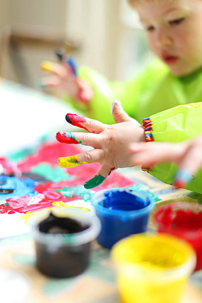 Child Painting with Colorful Fingerpaint stock photo