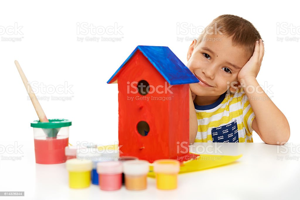 Child paints wooden birdhouse stock photo