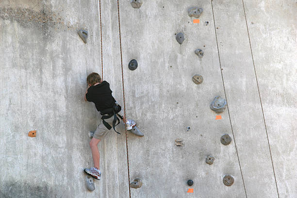 Child participates in rock climbing on outdoor facility