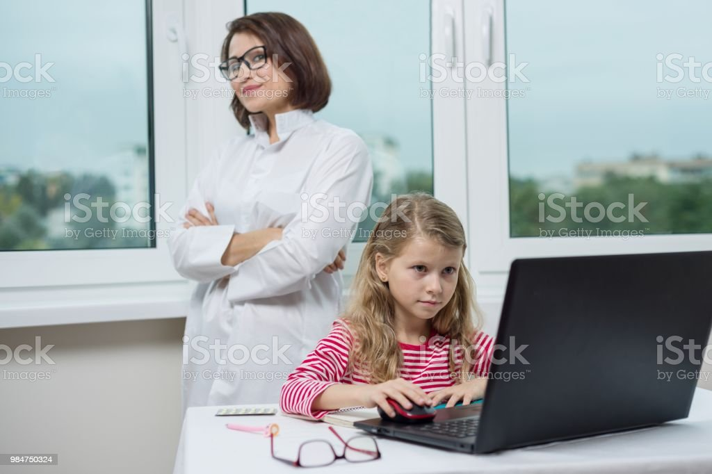 Child patient in the doctor office is sitting at the table, looking at the laptop.