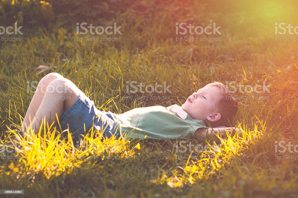 Child peacefully sleeps on nature stock photo
