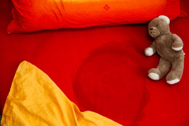 Kind pinkelt auf dem Bett – Foto