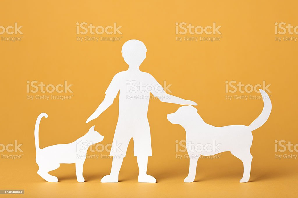 Child petting a dog and cat: paper concept royalty-free stock photo