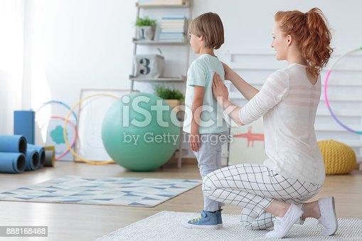 istock Child physiotherapist examining patient spine 888168468