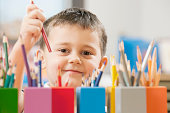 Child picking up colored pencil in school classroom