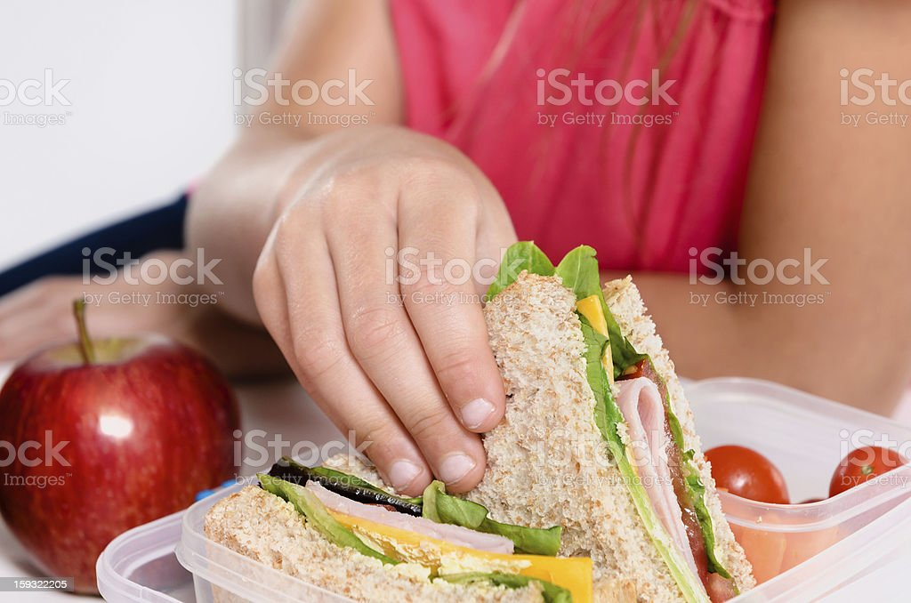 A child picking up half of a sandwich from their lunchbox stock photo