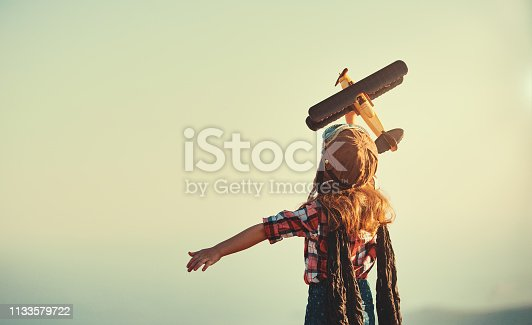 istock Child pilot aviator with airplane dreams of traveling in summer  at sunset 1133579722