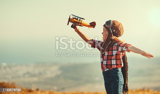 istock Child pilot aviator with airplane dreams of traveling in summer  at sunset 1133579750