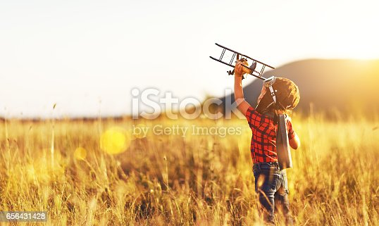 istock Child pilot aviator with airplane dreams of traveling in summer  at sunset 656431428