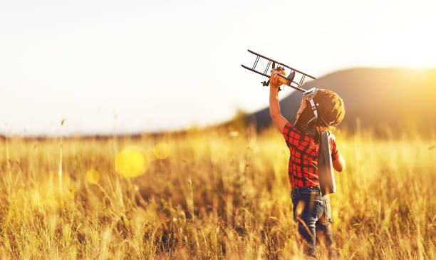 Child pilot aviator with airplane dreams of traveling in summer  at sunset stock photo