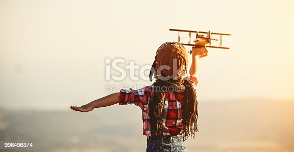 istock Child pilot aviator with airplane dreams of traveling in summer  at sunset 996496374