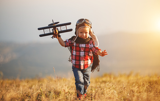 istock Child pilot aviator with airplane dreams of traveling in summer  at sunset 996505062