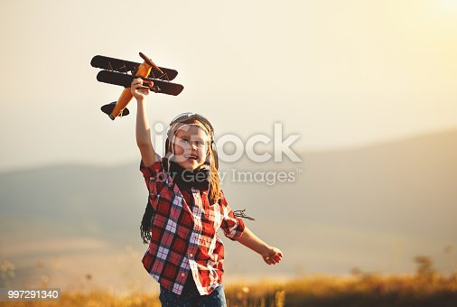 istock Child pilot aviator with airplane dreams of traveling in summer  at sunset 997291340