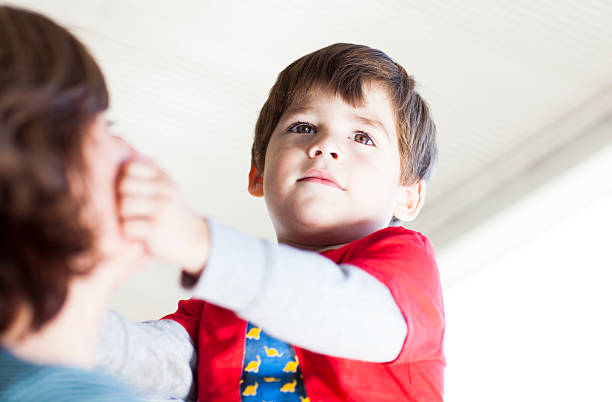 Child pinching the cheek of her mother stock photo