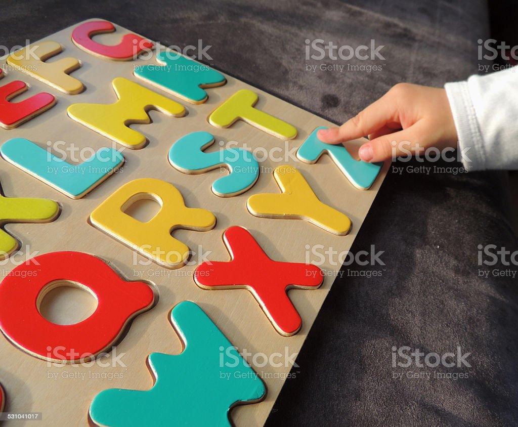 Child playing ABC Puzzle stock photo