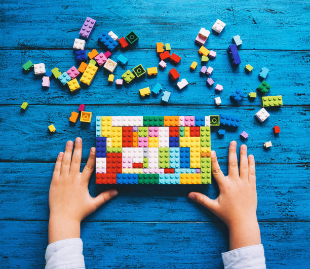 Child playing and building with colorful toy bricks or plastic blocks on table. stock photo