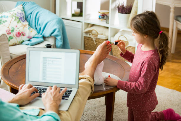 Child playing and disturbing father working remotely from home. stock photo