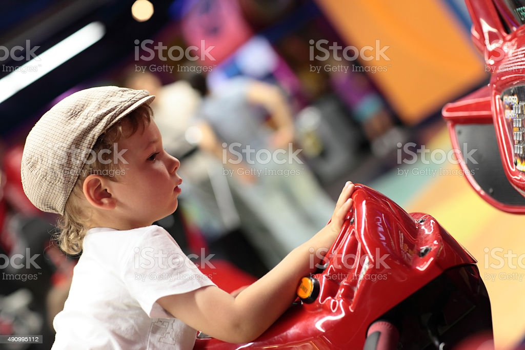 Child playing arcade simulator machine stock photo