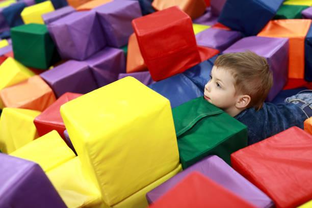 kind spielt am stoffwürfel - verwandlungskissen stock-fotos und bilder