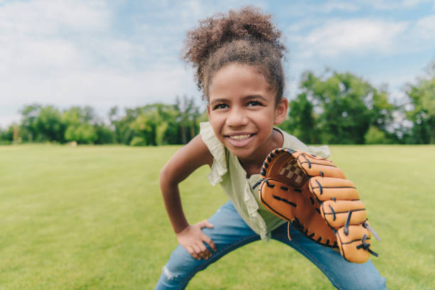 child playing baseball in park portrait of smiling african american little girl with baseball glove playing baseball in park baseball sport stock pictures, royalty-free photos & images