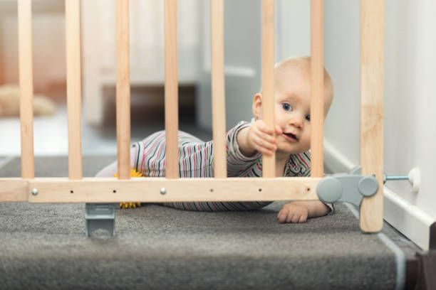 child playing behind safety gates in front of stairs at home - portão imagens e fotografias de stock