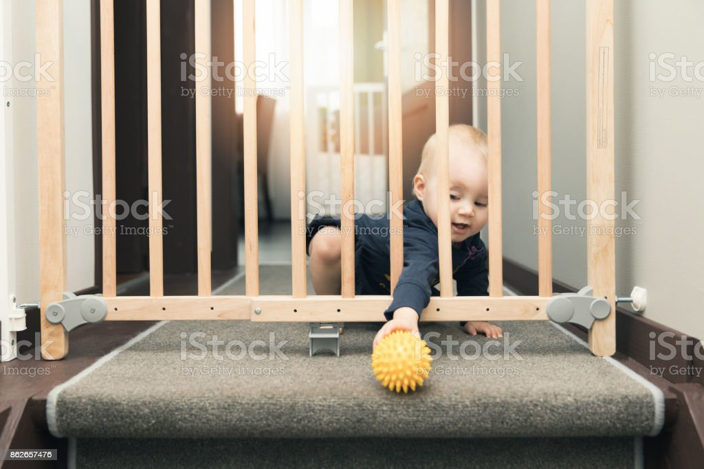 child playing behind safety gates in front of stairs at home stock photo