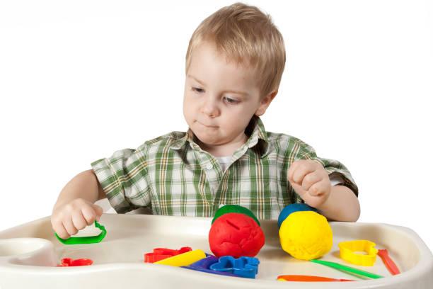 kind spielt farbe plastilin, kid guß multi farbe spielzeug tonkugeln, isoliert auf weiß - knete spiele stock-fotos und bilder