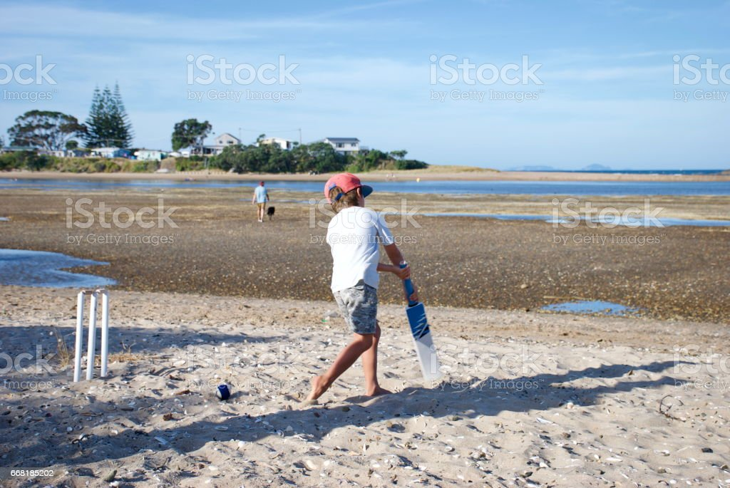Child playing Cricket on the Beach stock photo