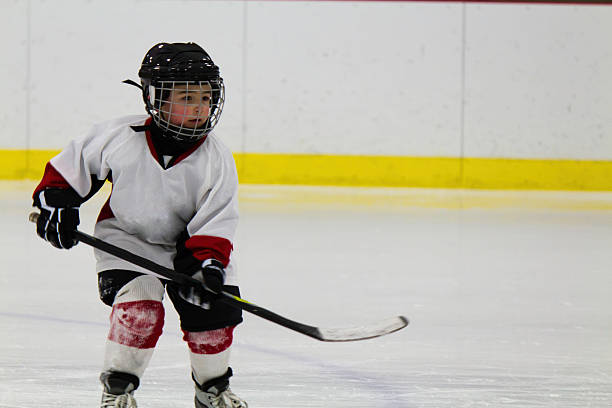 Child playing ice hockey in a white uniform  stock photo