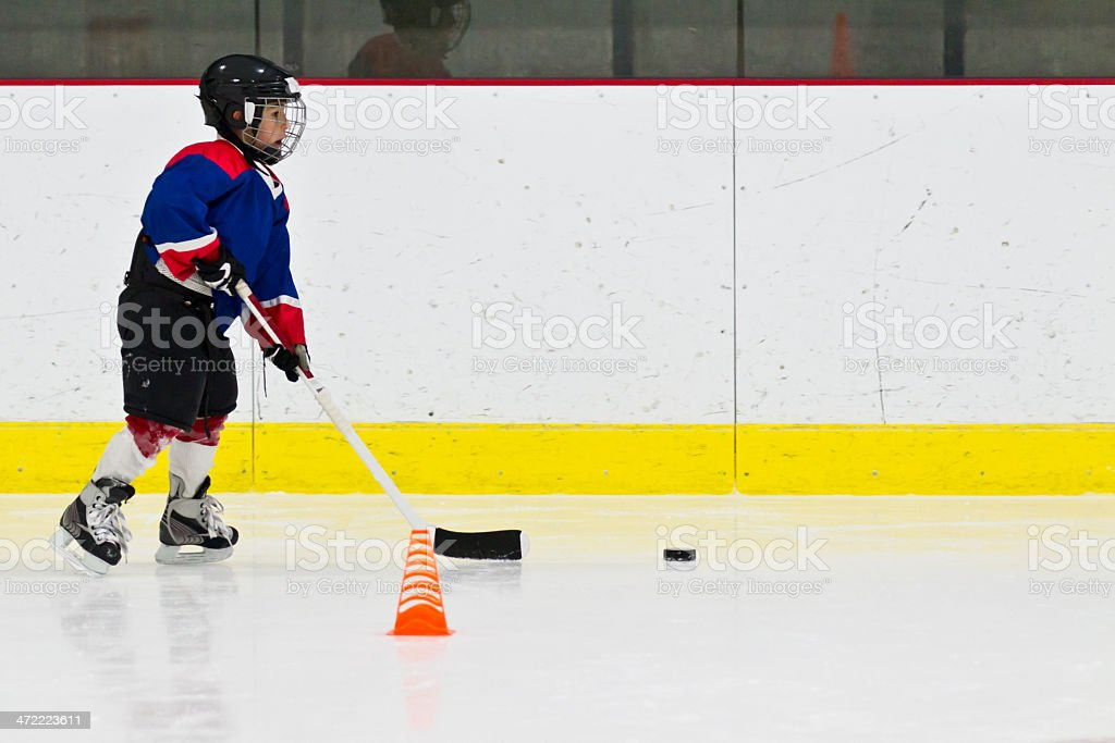 Child playing ice hockey practicing in full kit stock photo