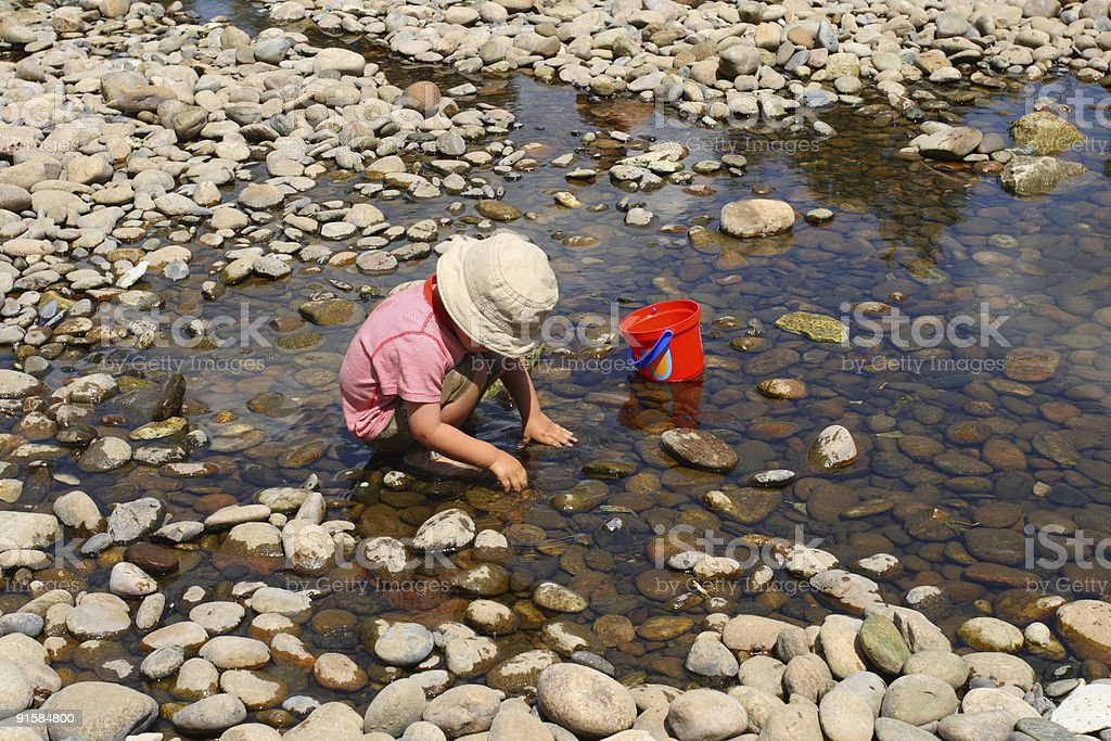 child playing in a dry river stock photo