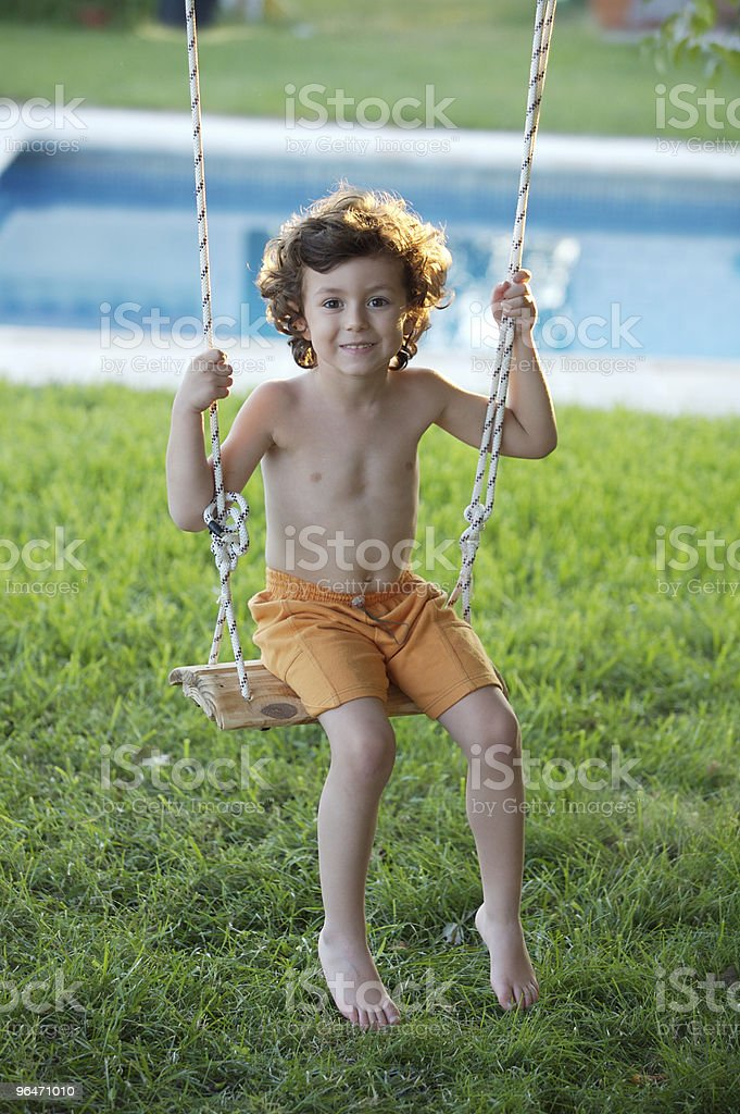 child  playing in a swing royalty-free stock photo