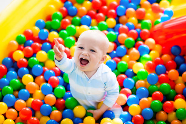child playing in ball pit on indoor playground - playpen stock pictures, royalty-free photos & images