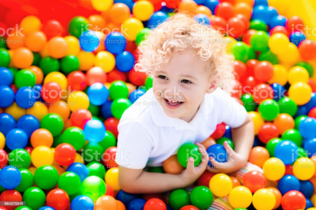 Child playing in ball pit on indoor playground stock photo