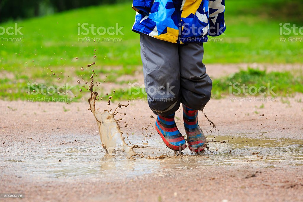 child playing in muddy puddle stock photo