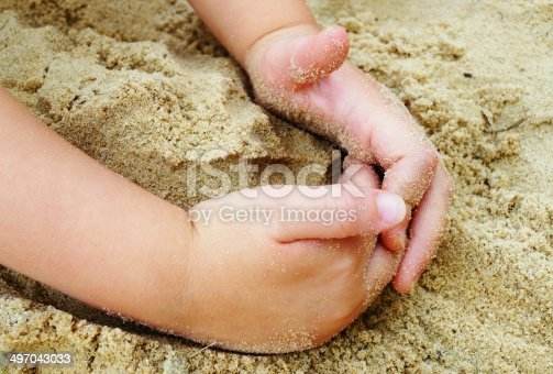 Small child hands playing in the sand at the beach.