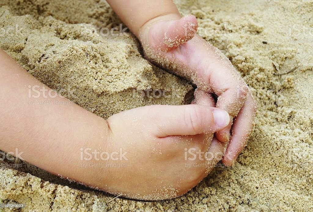 Child Playing in Sand at Beach stock photo