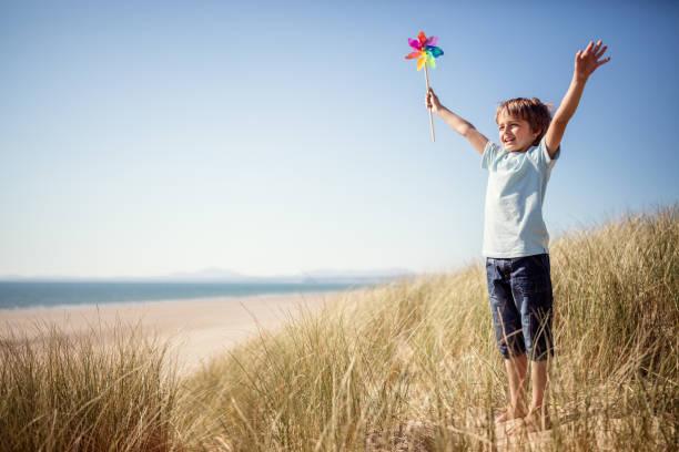 child playing in sand dunes at the beach on summer vacation - unschuldig stock-fotos und bilder