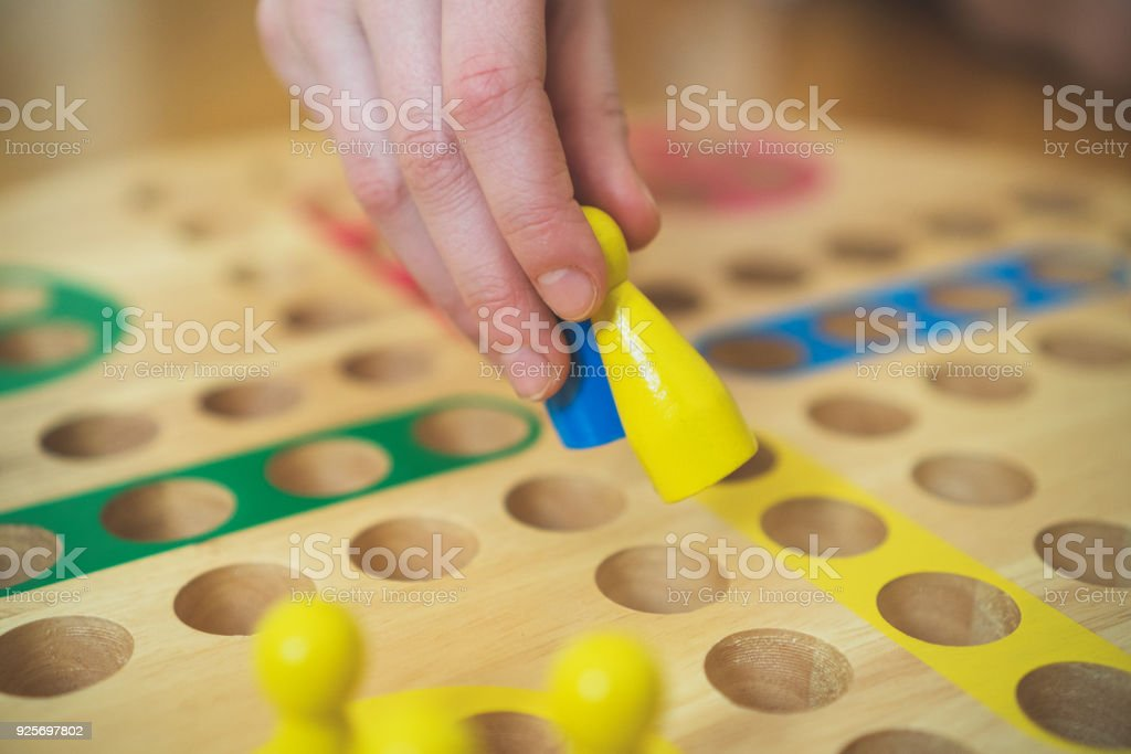 Child playing Ludo board game. Close-up view. stock photo