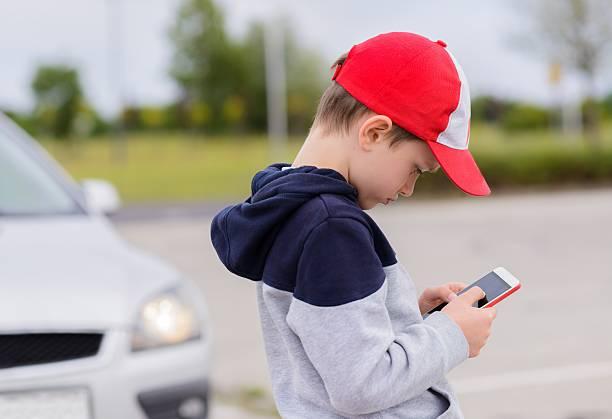 child playing mobile games on smartphone on the street - online spiele spielen stock-fotos und bilder