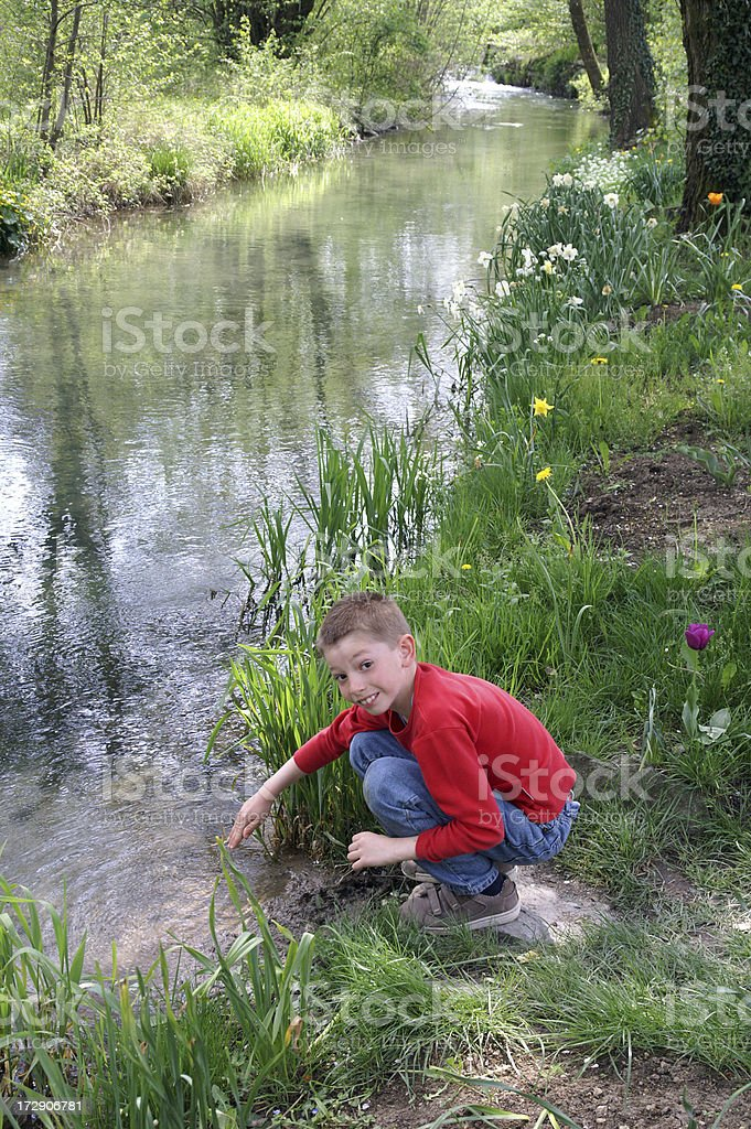 Child playing next to a stream royalty-free stock photo