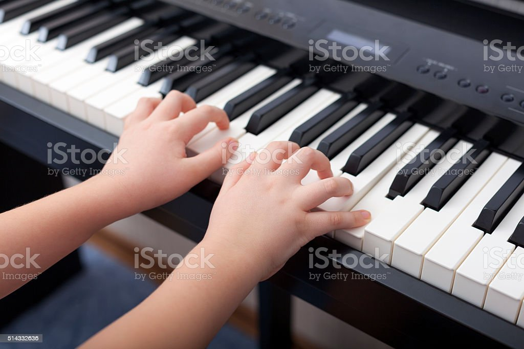 Child playing on a digital piano stock photo