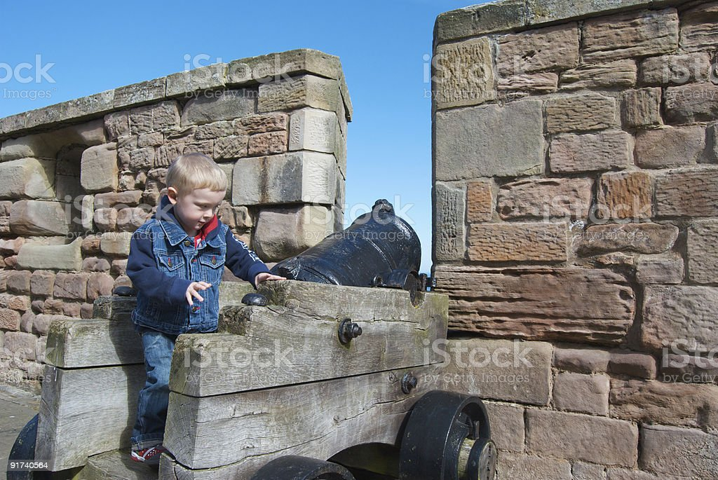 Child playing on an old canon at Bamburgh Castle royalty-free stock photo