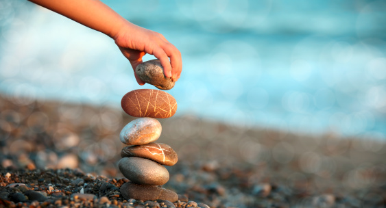 close up shot of child hand playing with stones on beach.