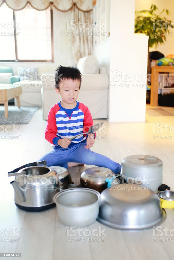 Child playing on floor with pots and pans stock photo