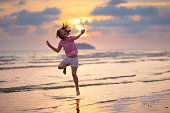 Child playing on ocean beach. Kid jumping in the waves at sunset. Sea vacation for family with kids. Little girl running on  exotic island during summer holiday.
