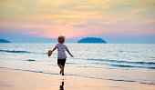 Child playing on ocean beach. Kid jumping in the waves at sunset. Sea vacation for family. Little boy running on exotic island during summer holiday.